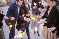 Group of friends waving sparklers, at party - CUF24334
