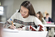 Smiling teenage girl writing in exercise book in class - ZEF15658