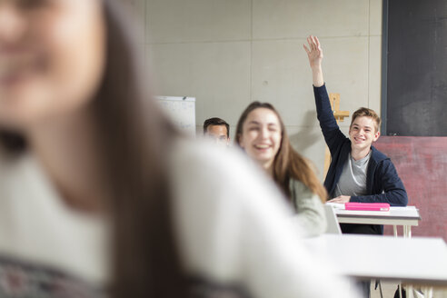 Smiling teenage boy raising hand in class - ZEF15661