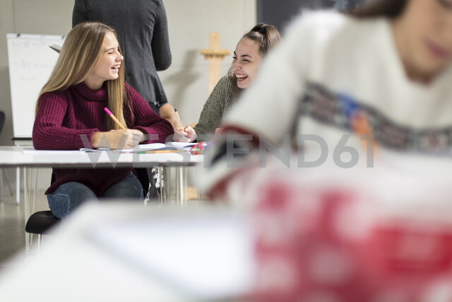 Happy teenage girls talking in class - ZEF15664