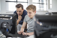 Teacher and student using computer in class - ZEF15700