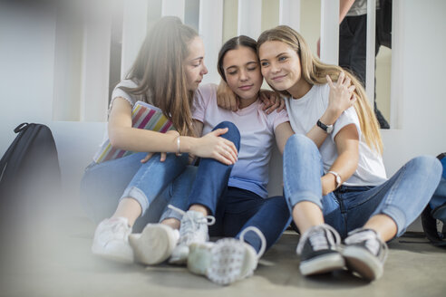 Smiling teenage girls sitting on floor in school hugging - ZEF15724