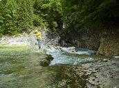 Austria, Tyrol, Brandenberg, man crossing Brandenberger Ache, splash water - CVF00738