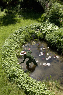 High angle view of mature woman in garden cleaning out pond - CUF24409