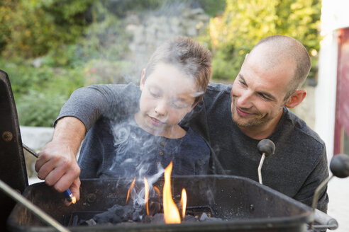 Mid adult man and son lighting barbecue in garden - CUF24424