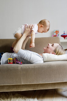 Mother lying on sofa, holding baby girl in air - CUF24550
