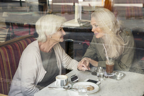 Mother and daughter sitting together in cafe, holding hands, seen through cafe window - CUF24661