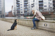 Mid adult woman and training her dog on city riverside - CUF24691