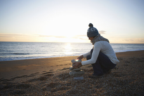 Mature woman stacking stones on beach at dusk - CUF24745