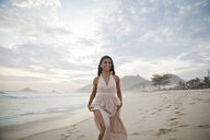 Mid adult woman walking along beach - CUF24763