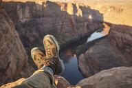 Man sitting on rock, close-up of feet, Page, Arizona, USA - ISF09380