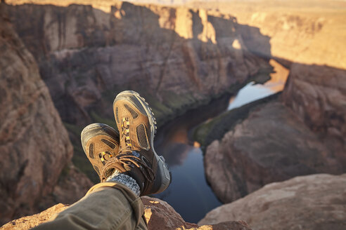 Man sitting on rock, close-up of feet, Page, Arizona, USA - ISF09380
