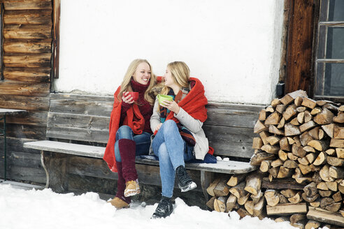 Two young female friends drinking coffee outside wooden cabin - CUF25025