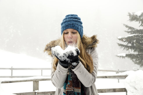Young woman blowing handful of snow - CUF25028
