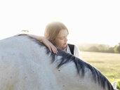 Portrait of teenage girl with grey horse - CUF25034