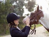 Teenage girl petting horse - CUF25037