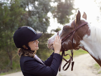 Teenage girl petting horse - CUF25037