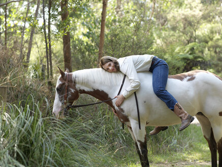 Portrait of teenage girl hugging horse whilst bareback riding - CUF25049