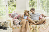 Young couple on living room sofa reading smartphone texts - CUF25169