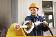 Worker using equipment in crane manufacturing facility, China - CUF25232