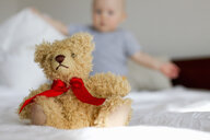 Cute teddy bear sitting up in bed in front of baby girl - CUF25259