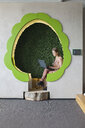 Designer working on laptop in tree shaped office space - CUF25328