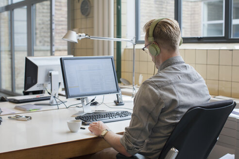 Rear view of man listening to headphones whilst working at office desk - CUF25334