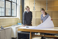 Two young designers looking at blueprint in creative office - CUF25349