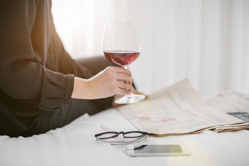 Cropped close up of mature businesswoman reading newspaper whilst drinking red wine in hotel room - CUF25361