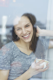 Portrait of young woman looking out of  apartment window drinking coffee - CUF25532
