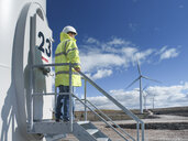 Engineer standing on stairway at windfarm - CUF25550