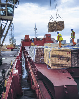 Workers unloading timber from cargo ship in port, Grimsby, England, United Kingdom - CUF25607