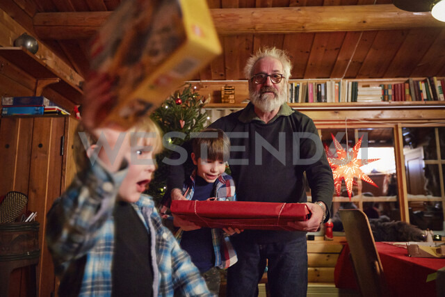 Joyful boy holding up Christmas present - CUF25625