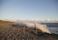 Boy and sister watching splashing waves from beach, Blowing Rocks Preserve, Jupiter Island, Florida, USA - ISF09428