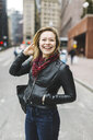 Portrait of woman in urban area looking at camera smiling, Boston, Massachusetts, USA - ISF09458