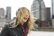 Woman with windswept blonde hair laughing, Boston, Massachusetts, USA - ISF09464