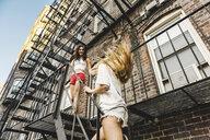 Women climbing fire escape ladder of apartment building, Boston, MA, USA - ISF09524