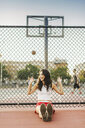Young woman leaning against fence of basketball court - ISF09533