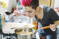 Young woman with pink hair smelling fried food on kitchen hob - ISF09542