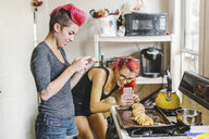 Two young women with pink hair taking smartphone photographs of stuffed baguette in kitchen - ISF09545