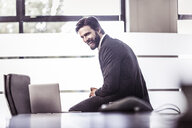 Businessman sitting on boardroom table laughing - CUF25813