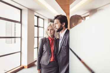 Portrait of businesswoman and businessman looking out of office window - CUF25828