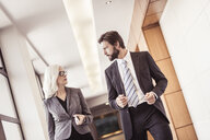 Businessman and woman walking and talking in office corridor - CUF25840