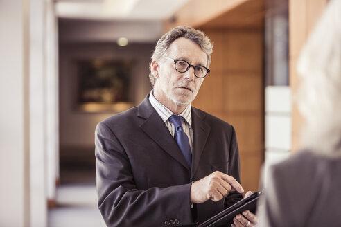 Over shoulder view of businessman using digital tablet in office corridor - CUF25843
