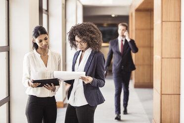 Young businesswomen reading paperwork in office corridor - CUF25849
