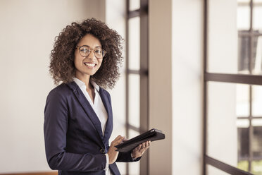 Portrait of young businesswoman using digital tablet in office - CUF25855