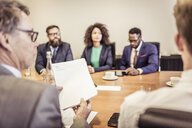 Over the shoulder view of businesswomen and men at conference table meeting - CUF25870