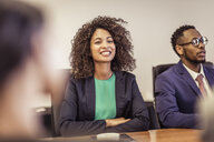Over shoulder view of young businesswoman at boardroom meeting - CUF25876