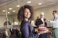 Young woman presenting cake with candles to business team in boardroom - CUF25885