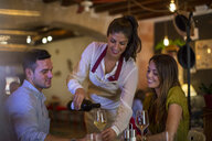 Waitress serving wine to customers in restaurant - CUF25897